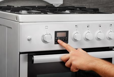 Weibliche Hand Öffnung Ofen In Weißen Küche Gasherd Auf Grauem ...