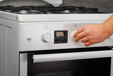 technic: Male hand turning on white kitchen gas stove on gray background