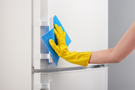thin ice: Womans hand in yellow rubber protective glove cleaning white refrigerator with blue rag on gray background