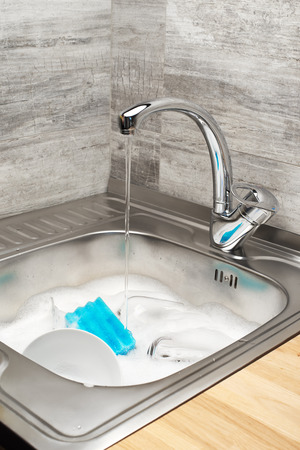 Close up of kitchen sink with running tap water full of foam, tableware and blue cleaning sponge Stock Photo
