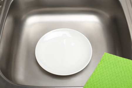 Close up of kitchen sink with clean white plate and green rag Stock Photo
