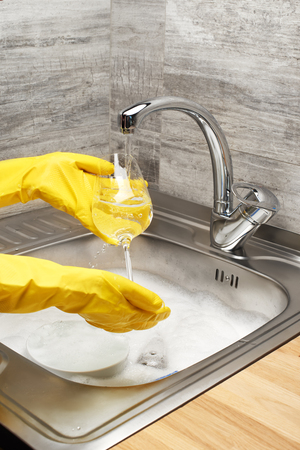 Close up of female hands in yellow protective rubber gloves washing wine glass under running tap water against kitchen sink full of foam and tableware Stock Photo