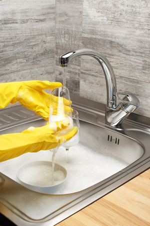 Close up of female hands in yellow protective rubber gloves washing drinking glass under running tap water against kitchen sink full of foam and tableware