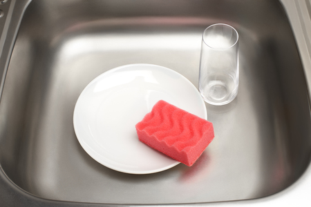 Close up of kitchen sink with clean white plate, pink cleaning sponge and drinking glass Stock Photo