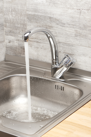Close up of kitchen sink with running tap water