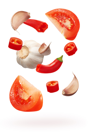 Cut red chili pepper vegetables, garlic with cloves and slices of tomato isolated on white background