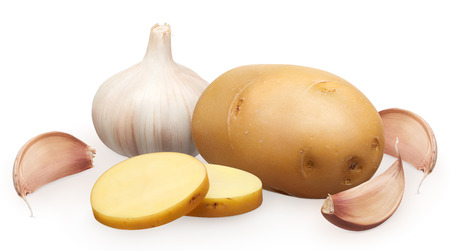 Whole fresh unpeeled potato with two chopped pieces and garlic with cloves isolated on white background Stock Photo