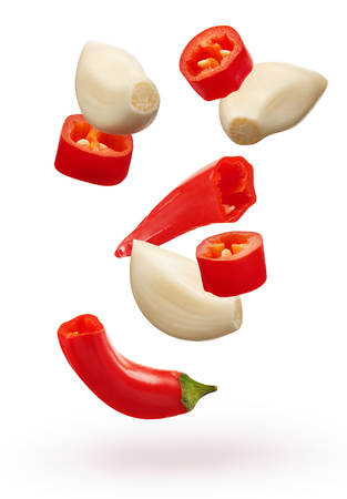 Pieces of chopped red chili pepper vegetable and three peeled cloves of garlic isolated on white background