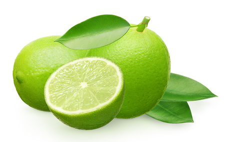 Whole fresh lime fruit next to lime lying on its side, half and green leaves isolated on white background