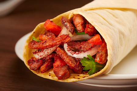 Clouse up of delicious shawarma with meat, tomato, onions and parsley on dark wooden table background. Dishes of oriental cuisine, eastern food. Stock Photo