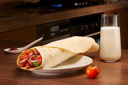 Delicious shawarma with meat, tomato, onions and parsley on white porcelain plate, sauce and glass of milk on dark wooden kitchen background. Dishes of oriental cuisine, eastern food.