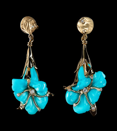 Luxury gold earrings in shape of light blue flower with diamonds isolated on black background. Love and wedding concept.