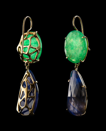 Luxury gold earrings with green and blue natural gemstones isolated on black background. Love and wedding concept.