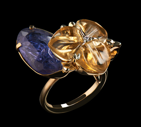 Luxury gold ring with yellow and blue natural gemstones and diamonds isolated on black background. Love and wedding concept.