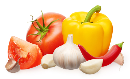 Whole fresh red tomato with green leaf and slice, yellow bell and red chili peppers and garlic with cloves isolated on white background