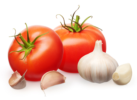 Two whole fresh red tomatoes with green leaves and garlic with cloves isolated on white background