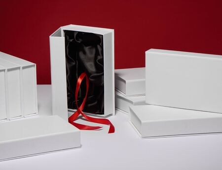 White gift boxes with black silk lining and red ribbon on red background