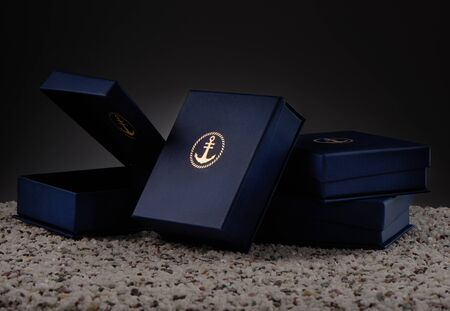 Blue gift boxes with emblem of golden anchor on sea pebbles Stock Photo