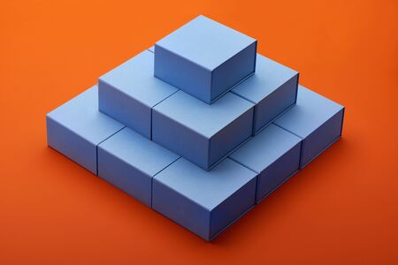 Pyramid of light blue gift boxes on  bright orange paper background
