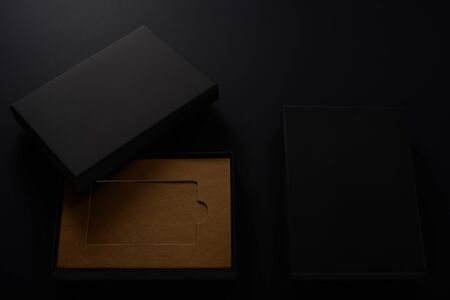 Slick black gift boxes with brown cardboard inside on black background Stock Photo