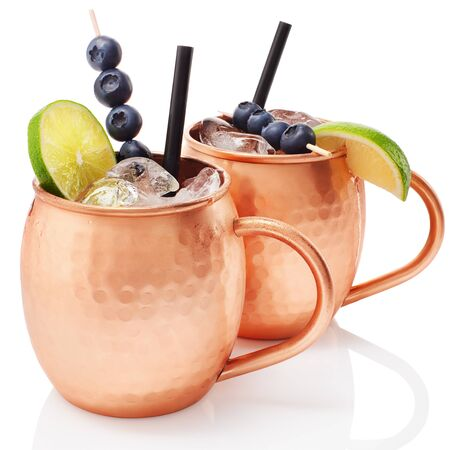 Icy cold Moscow mule cocktail with ginger beer, vodka, lime and blueberries in copper mugs with reflection isolated on white background