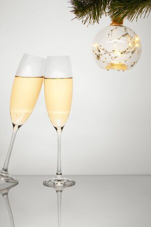 Two glasses of champagne with reflection and transparent ornament with gold sparkle lightened up star garland hanging from Christmas tree branch isolated on white background. Clipping path included. Stock Photo