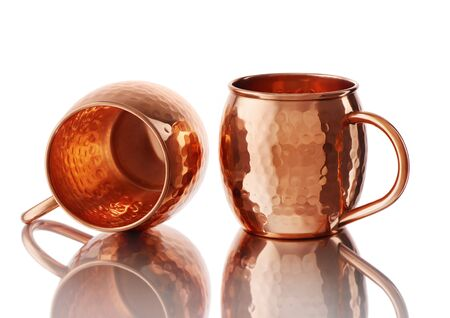 Empty copper mugs for cold and hot drinks with reflection isolated on white background