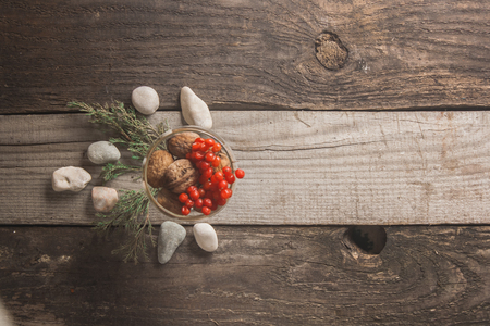 basket weaving: Kitchen Still Life. Filmed with berries and sea stones on a wooden background texture with green branches and walnuts