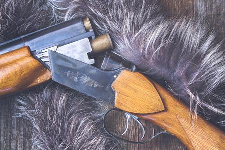 fusil de chasse: Fusil de chasse sur un fond de bois.