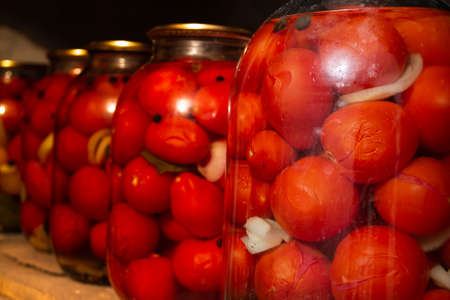 Photo of canned vegetables, in an old cellar with dim lighting, and with wooden shelves