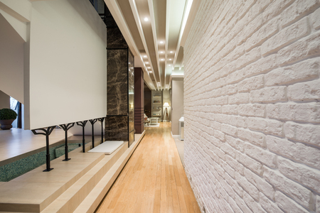 brick house: Interior of a long corridor with white brick wall
