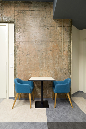 Blue chairs and table in front of a concrete wall in office interior