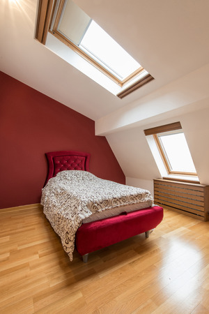 Bedroom interior in luxury red loft, attic, apartment with roof windows