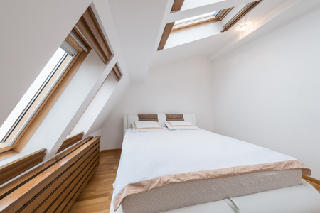 Bedroom interior in luxury loft, attic, apartment with roof windows 스톡 콘텐츠