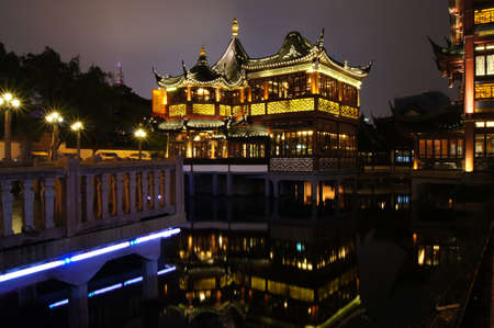 Chinese Garden Yuyuan in Shanghai at night  View on Huxinting Teahouse  Huxinting Chashi   The Huxinting Teahouse is an attractive pagoda style building in centre of picture  photo