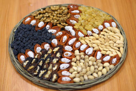 A national uzbek woven plate with dried fruits (prunes, raisins, dried apricots) and nuts (walnuts, almonds, pistachios). photo