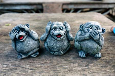 3匹の猿は、悪を見ない、悪を聞く、悪を話さないという概念を持つ手の小さな彫像を閉じます。 写真素材