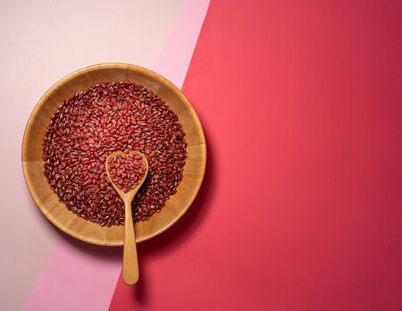 Grains Red bean in wooden bowl and hart spoon putting on isolate pink, red background 免版税图像