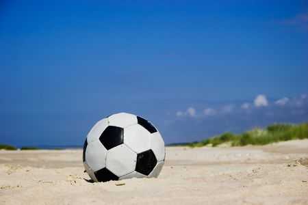 Soccer ball on sandy beach after game