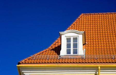 Flashing orange tiled roof on blue sky and one garrret window in Riga old town, Latvia Stock Photo - 736591