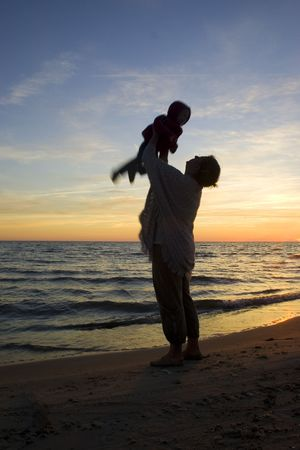 Mother and child playing in sunset photo