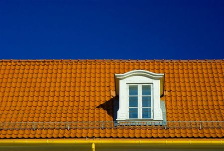 flashing: Dormer roof window, in a flashing orange tiled roof on blue sky