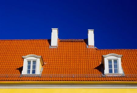 residency: Orange roof with two windows and chimneys against blue sky Stock Photo