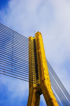 Modern Yellow Cable bridge closeup on blue sky photo