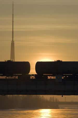 Silhouette of freight tank wagons on a bridge. Morning Sunrise. In background TV tower photo