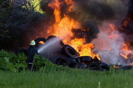 public insurance: Firefighters battle with burning tires Stock Photo