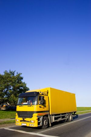 Yellow truck on asphalt road. Large blue sky with place for copy text.