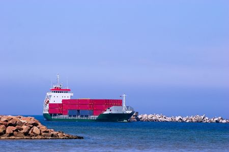 tonnage: Cargo ship with red containers entering port
