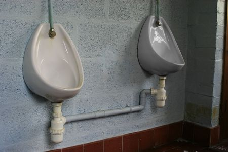urination: Two porcelain urinals on blue wall in men restroom