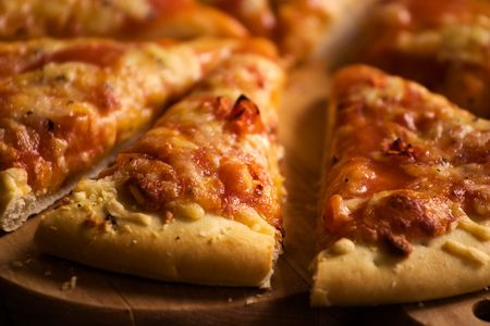 Pieces of cheese pizza on wooden plate Stock Photo - 907651